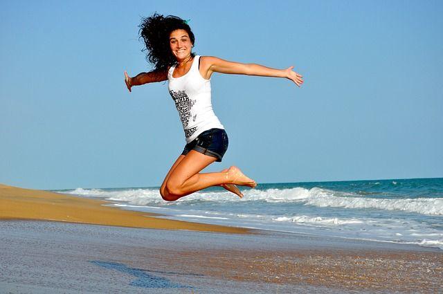 Frau springt am Strand in die Luft