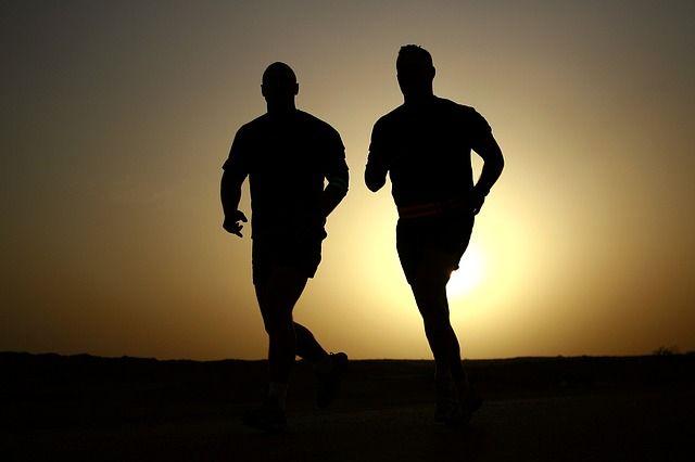 Zwei Männer laufen am Strand im Sonnenuntergang