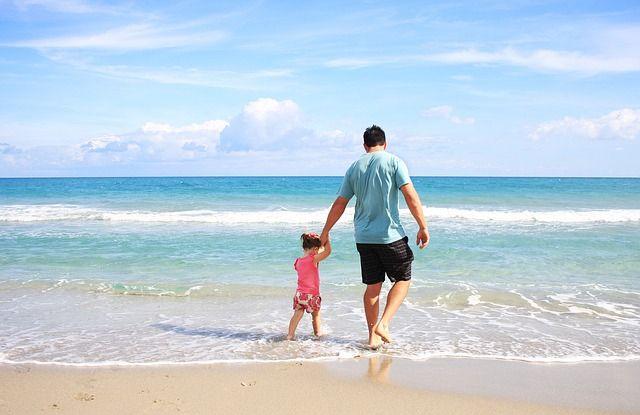 Vater läuft mit Tochter am Strand
