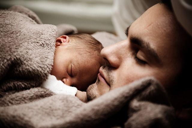 Ein Baby schläft auf der Brust des Vaters